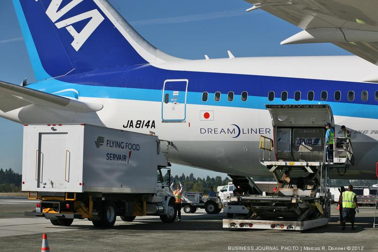 Workers with Swissport, at right, prepare to unload cargo from an ANA 787 in 2012. According to Sound Progress, Swissport is one of many contractors at Seattle-Tacoma International Airport that would be affected by a higher minimum wage in the city of SeaTac.