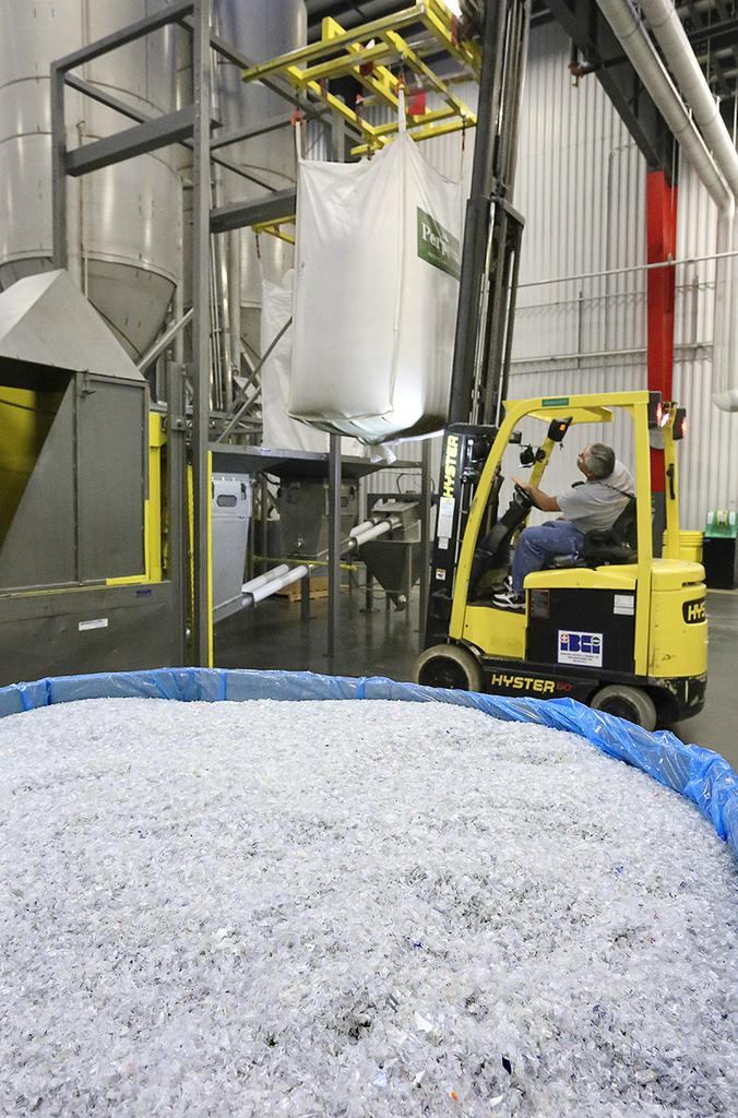 Jerry Sapp, forklift operator, places a bag of plastic flake set to be melted and transformed into REPREVE yarn at Unifi's Yadkinville plant. Plastic flake, seen in the foreground, is chopped up plastic bottles.