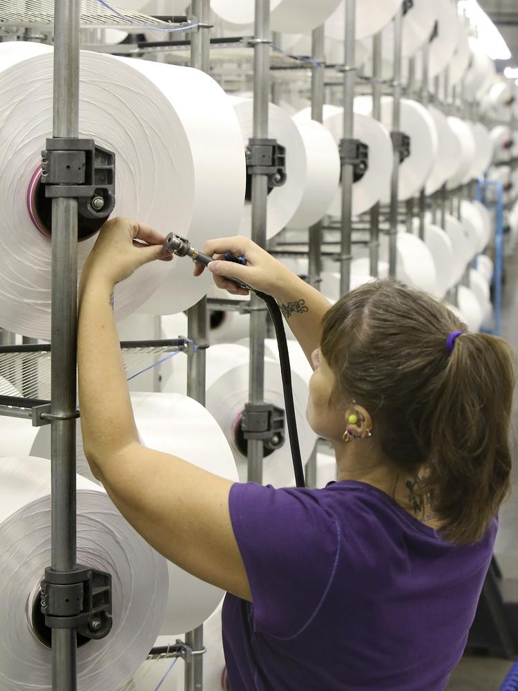 Jennifer Barringer creels REPREVE yarn at Unifi's Yadkinville plant. REPREVE yarn is 100 percent recycled polyester yarn that can used with furniture fabric.