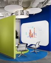 Intimate collaborative spaces incorporate bright colors, white boards and whimsical light fixtures.