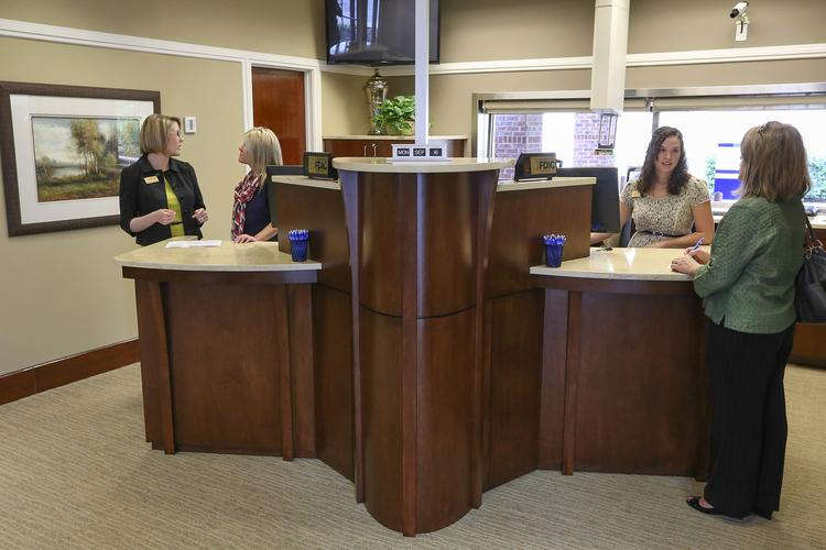 The newly opened branch of High Point Bank on Stratford Road in Winston Salem incorporates a new design element, teller pods to give customers a bit more privacy. Here, Stephanie Millirons (left), office manger of the barnch, works with customer service representative Misty Gordy , while customer service representative Amanda Kivett assists a customer.