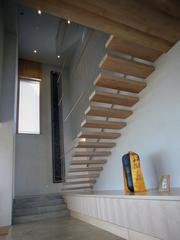 FSC wood comprises materials of Eric Lemelson's Karuna House's maple stair treads and cabinets. The treads are supported by internal steel plate and visible stainless steel rods.