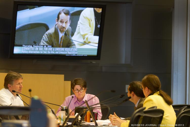 Seattle City Council members discuss ride sharing policies during a September meeting. Regulated taxi and limo services feel threatened by the unregulated ride-sharing companies which have sprung up like UberX, Lyft and Sidecar.