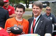 Clark Hunt joins a young fan in the parking lot before the Kansas City Chiefs' 2013 home opener against Dallas on Sept. 15.