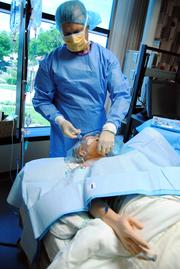 Dr. Jamal Hakim demonstrates the sterile procedures necessary for the insertion of a central line.