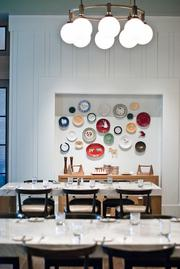 "Plates decorate a wall to bring a ""home kitchen"" feel to the dining space."