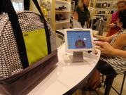 iPads enhance the millennial-friendly feel of the store. Shoppers can design custom Kate Spade Saturday Weekender bags (on left) online with color, print, and monograms.