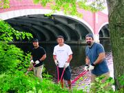 DOWN BY THE BANKS OF THE RIVER CHARLES: Volunteers from Intercontinental Real Estate Corp. spent a day along the Charles River picking up trash, gardening, weeding, and making sure that the river was in the best shape possible. From left are: Jorge Molina, Markus Echeverri and Dan George.