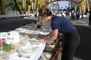 Lisa Moor-Turiello of Mulvaney's B&L adjusts place settings in preparation for the Tower Bridge Farm-to Fork dinner.