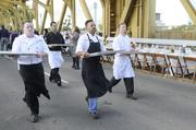 Servers begin delivering food to food stations in preparation for the Farm-to-Fork dinner on the Tower Bridge.