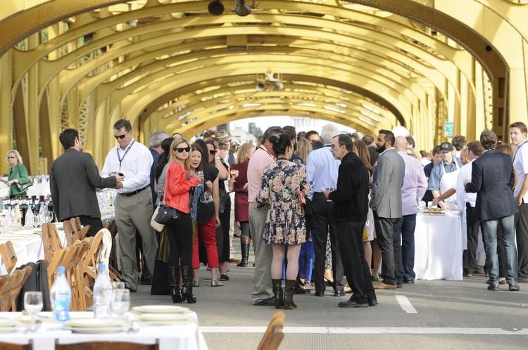 Dinner guests at the Tower Bridge Farm-to-Fork gala stand on the bridge.
