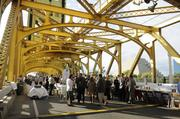 Dinner guests at the Farm-to-Fork dinner on the Tower Bridge begin looking for their seats.