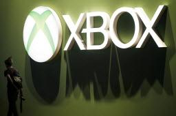 A visitor walks past an Xbox logo at Microsoft Corp.'s display booth during the Eurogamer Expo 2013.