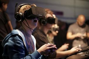 Gamers wear high-definition virtual reality (VR) headsets, manufactured by Oculus VR Inc., as they play Gaijin Entertainment's