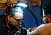 Robbie Ripoll, left, draws a tattoo during the Jacksonville Tattoo Convention.