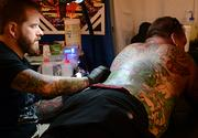 Justin Dale, left, draw a full-body tattoo on Iceman, right, during the Jacksonville Tattoo Convention.