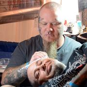 Bobby Tinker, top, draw a tattoo on the head of Rhett Lees, bottom, during the Jacksonville Tattoo Convention.