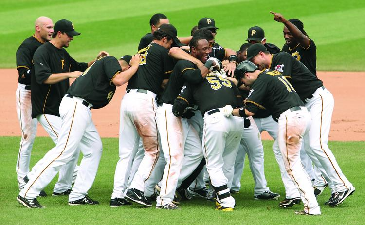 Pittsburgh Pirates catcher Russell Martin (55) is swarmed by teammates after Martin got a walk-off, 10th inning RBI to give the Pirates a 5-4 win over the Miami Marlins August 8. 2013 at PNC Park. Martin came to the PIrates as a free agent in the off season and has been instrumental in the pennant chase.  JOE WOJCIK PHOTO