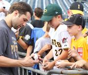 Former Pine-Richland Ram and Pittsburgh Pirates second baseman Neil Walker signs autographs during batting practice at PNC Park Aug. 28.