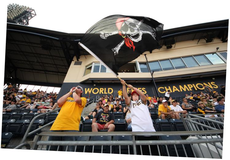 """Austin McCoy, 13, of Freedom, Beaver County, waves the Jolly Roger late in the Pirates-Marlins game Aug. 8  at PNC Park. Austin's father, Jess, 42, at left, was only nine years old when the Pirates last won a World Series, in 1979.  """"I didn't watch it, """" the elder McCoy said. """"But I remember my Dad watching it."""""""