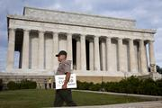 A Park Service officer carries closure signs in front of the Lincoln Memorial.