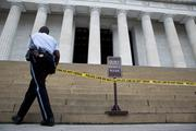 A member of the Park Police places police tape in front of the Lincoln Memorial.