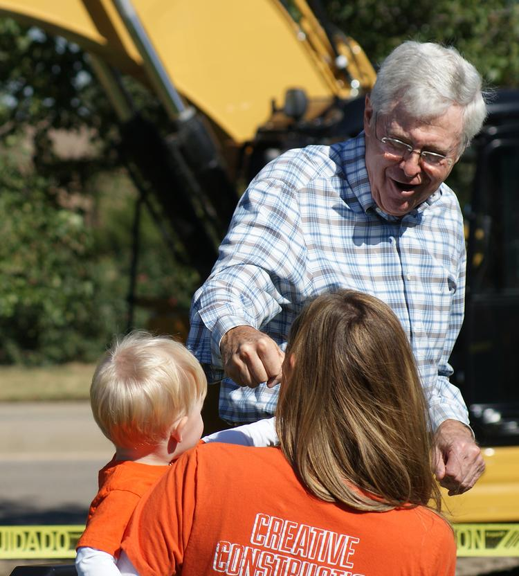 Charles Koch offers a fist bump to grandson Charlie during the a ceremony to mark the groundbreaking of a headquarters expansion.