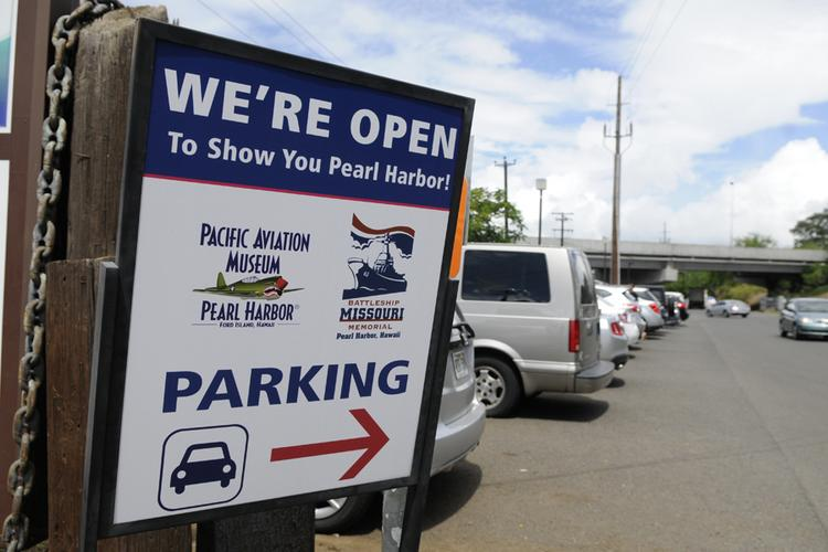 A sign outside the parking lot for the Battleship Missouri Memorial and the Pacific Aviation Museum Pearl Harbor told visitors both attractions were open for business on Tuesday, despite a shutdown of the federal government that closed the USS Arizona Memorial and other Pearl Harbor historic sites.