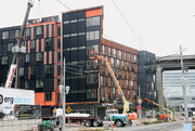 Workers install a metal exterior at The Emery, the project completed at Zidell Yards at Portand's South Waterfront.