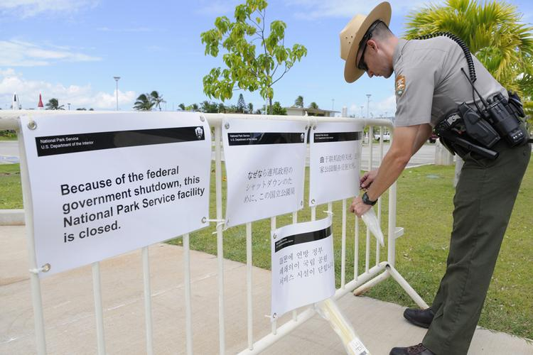M. Leon, a park ranger with the National Park Service, posts signs Tuesday letting visitors to the World War II Valor in the Pacific National Monument at Pearl Harbor know it was closed due to the federal government shutdown.