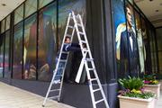 Jason Hallgren from Fastsigns of Kirkland installs a vinyl mural on the windows of a new Rainer Square store called Suitsupply on Fifth Avenue north of Rock Bottom.