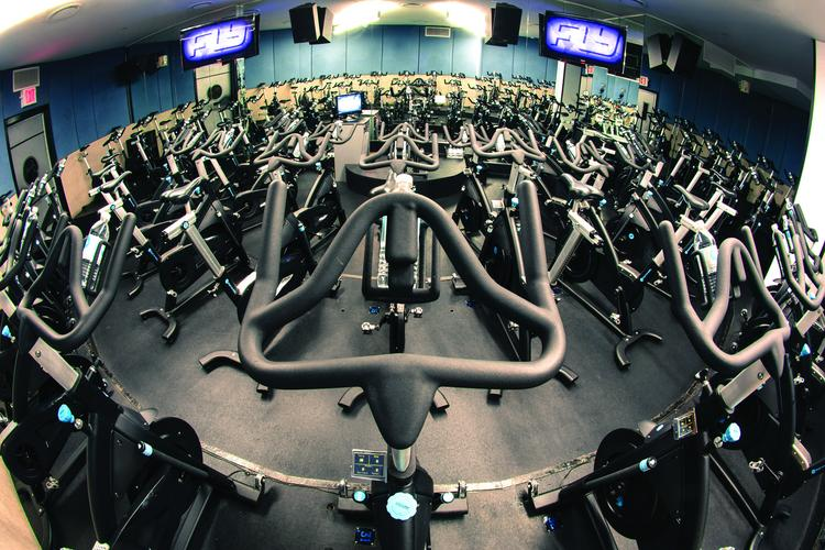 Flywheel studios feature stadium-style seating arrangements and a scoreboard to track riders' fitness.