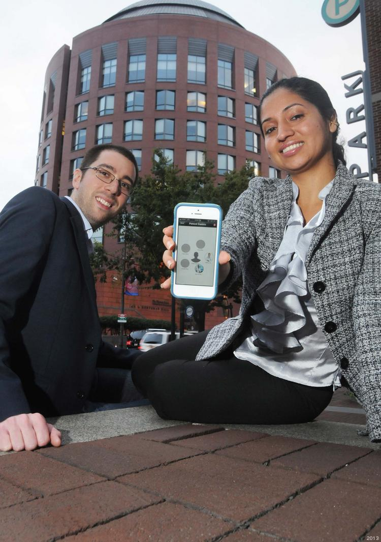 Lane Rettig and Dr. Divya Dhar near the Wharton School, where they thought the idea up for Seratis.  Dhar is holdinga smartphone showing the template for how the app works.