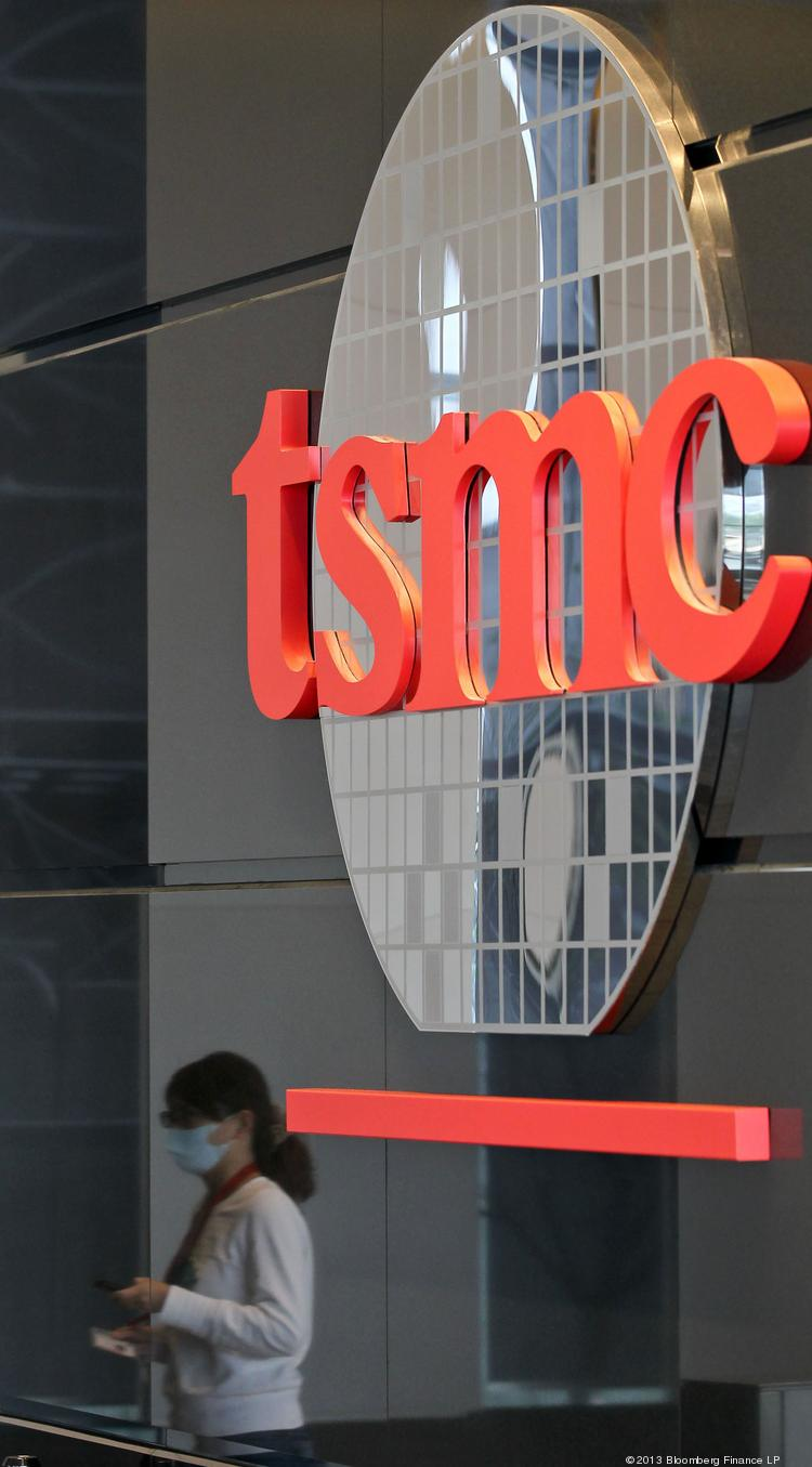 The Taiwan Semiconductor Manufacturing Co. logo is displayed as an employee is reflected entering the company's headquarters in Hsinchu, Taiwan, in January. Washington Gov. Jay Inslee will visit the company's WaferTech plant in Camas Friday as speculation mounts that TSMC could expand its operations there.
