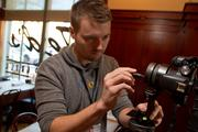 Carper cleans his wide angle lens as he prepares to shoot at Ted's Montana's Grill in the Arena District.