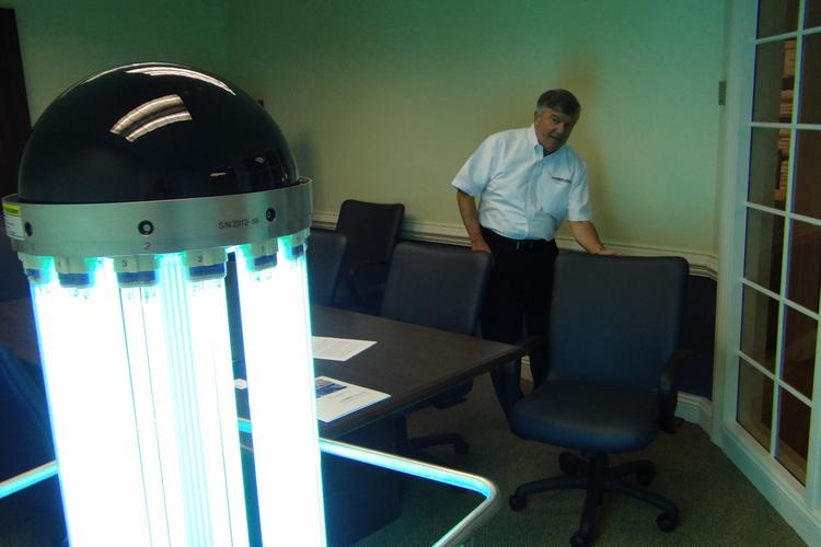 Bob Taylor, national sales director for Lumalier, demonstrates how the UV light from the Tru-D SmartUVC Room Disinfection system reflects off the walls to disinfect a greater range of surfaces.