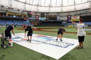 At Tropicana Field, Rays groundskeepers Chris Bonneau, James Michael, Mike Deubel and Jason Hess paint along the first base line.