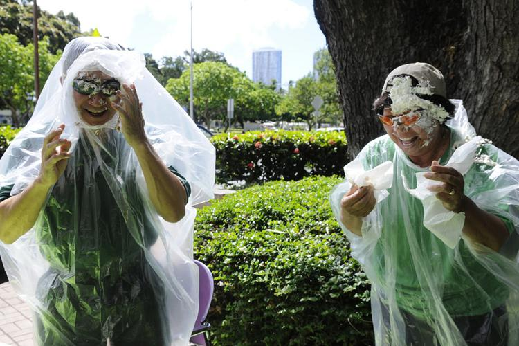 """Allen Uyeda, left, president and CEO of First Insurance Company of Hawaii, and Assistant Vice President of Commercial Underwriting Wenda Araki participate in the company's """"Pie-A-Friend"""" event that benefited the Aloha United Way. Employees paid $5 to be able to put a pie in the face of a person who was voted to be pie-d by FICOH associates."""