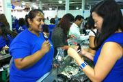 Bank of Hawaii Wealth Administrator Lachmin Singh holds up a mirror for a customer at the jewelry counter at Goodwill Industries of Hawaii's Goodwill Goes Glam! VIP event, sponsored by Bank of Hawaii, at the Neal S. Blaisdell Exhibition Hall.