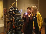 Maribeth Graybill (right), curator of the Asian art collection for the Portland Art Museum, uses a pen light to highlight the fine detail of silk ties on the a piece of armor for Elizabeth Thomas.