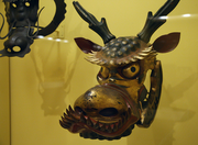 A 19th century dragon horse mask made of leather and lacquered in gold, red and black.