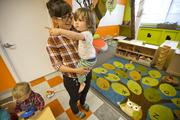 A NextKids caregiver holds a toddler at the daycare facility. The company is currently seeking caregivers to keep up with demand for the service, though hiring can be a challenge since the company seeks individuals with advanced degrees who are well-versed in play-based educational curricula.