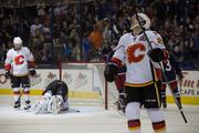 Flames forward Curtis Glencross watches for the replay while MacDonald picks himself back up.