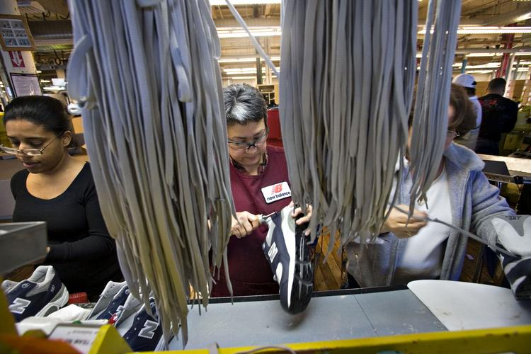 Esperanza Uspina, center, prepares a shoe for lacing inside the New Balance shoe factory in Lawrence, Mass., in this photo from January 2008. New Balance is opposed to reducing tariffs on footwear made in Vietnam, saying they compel companies to keep some of those manufacturing jobs in the U.S.