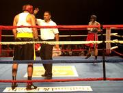 A boxer waits as the referee counts during a break in the match.
