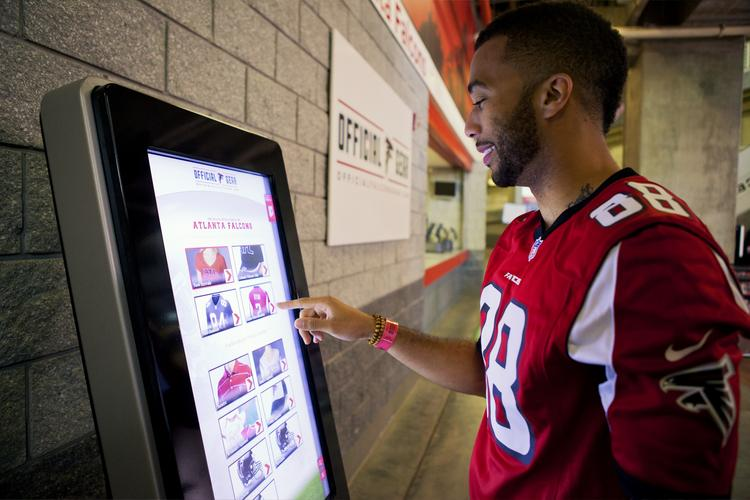 An Atlanta Falcons fan uses self-service technology from Duluth, Ga.-based NCR to select, purchase and pick up merchandise at the Georgia Dome during the game. Fans will spend less time in line and more time in their seats watching the game.