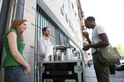 """Chris Davis, right, buys some tea from David Bley and Laura Walker at Fivezies and tea and coffee stand on Third Avenue North as part of the """"REVIVE: The Street Life Project"""" Friday. Bley says he hopes to have his bicycle cart version of the tea and coffee stand up and running by the end of the month."""