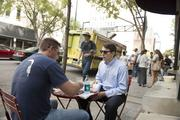 """(left to right) Matt Mogle and Austin Hardison eat in front of the Freshfullly pop-up shop on Third Avenue North as part of the """"REVIVE: The Street Life Project"""" Friday."""