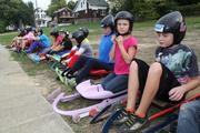 Kids put their helmets on in preparation to try luge.