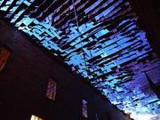 """An Inversion (with sky and land)"" by Micah & Whitney Stansell. This installation video projected onto of hundreds of white flags fluttering above a section of street mimics a daytime sky at night."